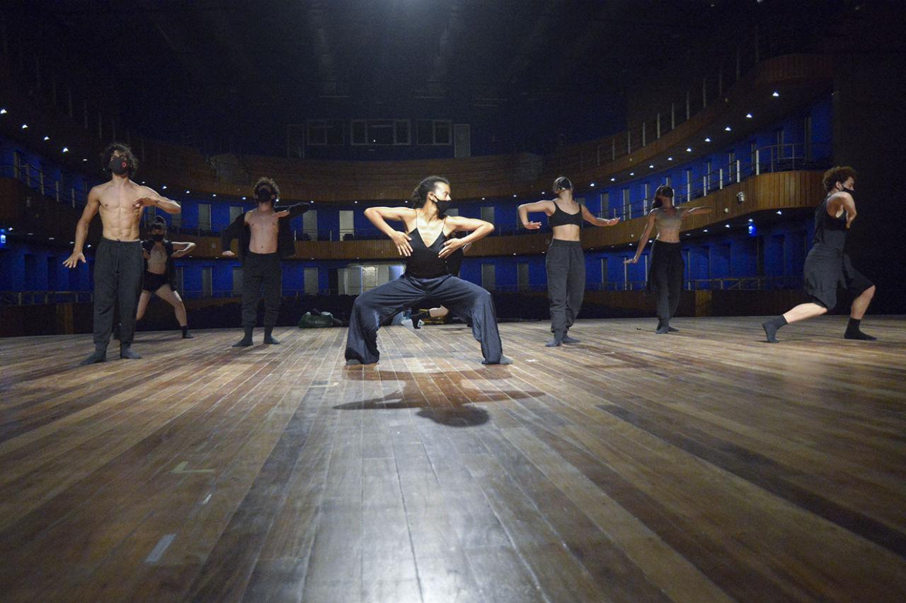 Bailarinos usando máscaras de proteção no rosto, em performance sobre palco de teatro, com plateia vazia ao fundo