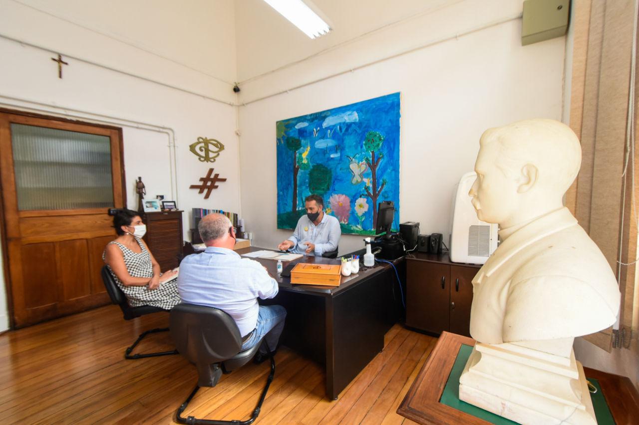 Busto em pedra de homem de lado em primeiro plano com dois homens e uma mulher ao fundo em reunião, em torno de uma mesa de trabalho
