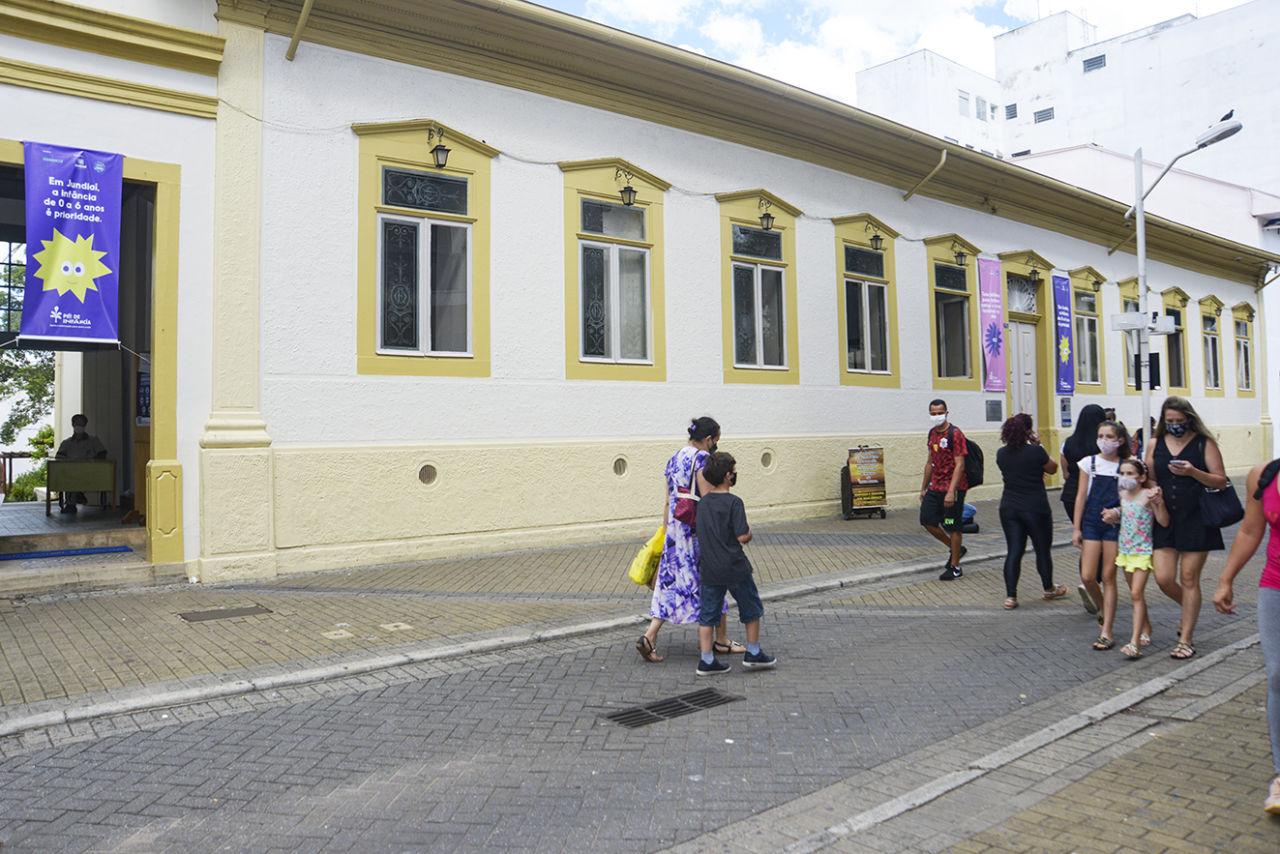 Pedestres com máscaras e sacolas nas mãos transitando sobre rua e calçada em frente a prédio histórico com banners verticais coloridos.