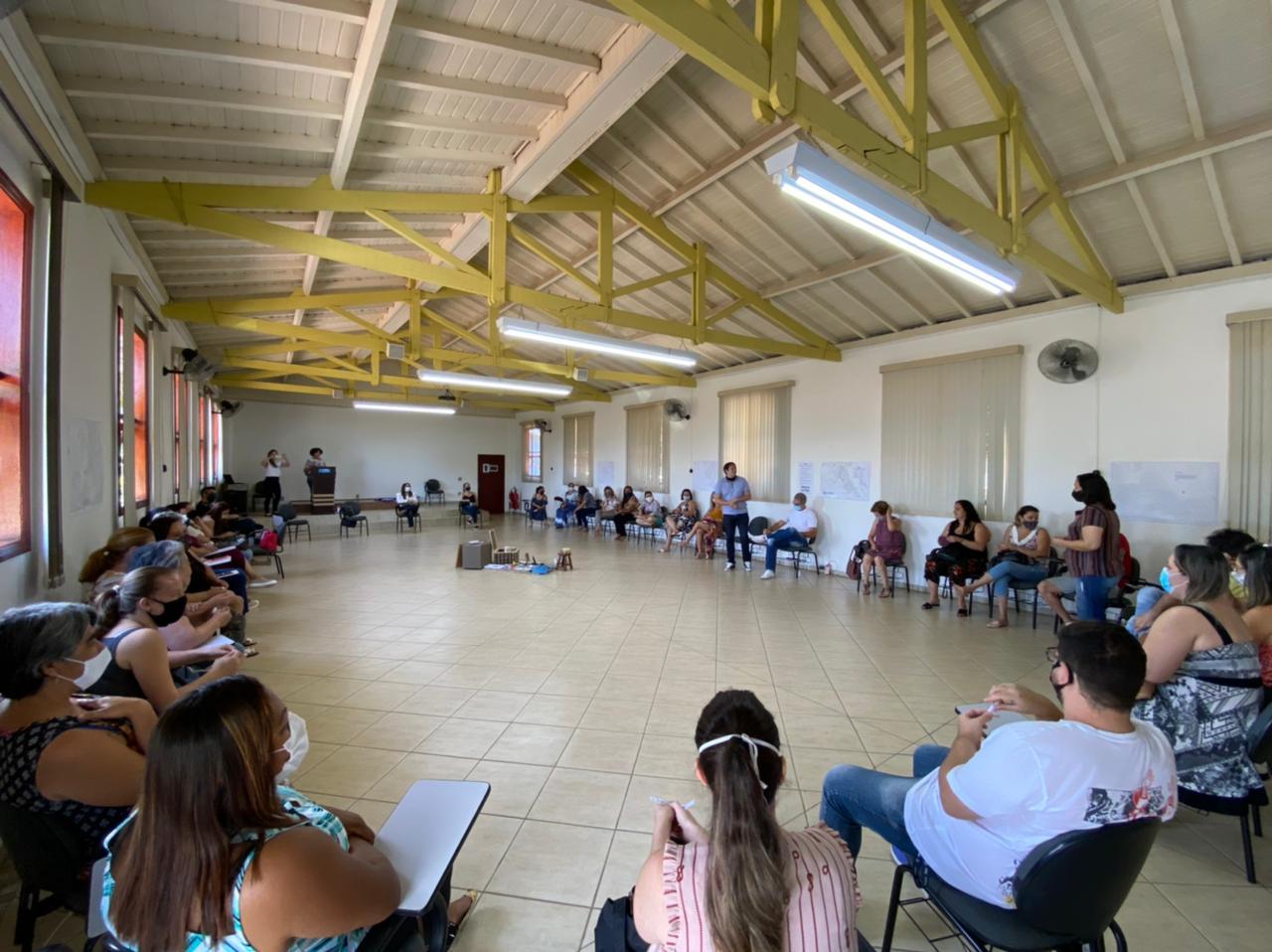 Imagem mostra uma sala com pessoas sentadas em roda.