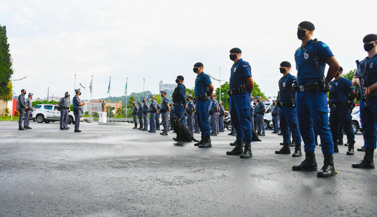 Foto de policiais com farda perfilados, um deles segurando um cachorro com coleira, com prédios e mastros com bandeiras ao fundo