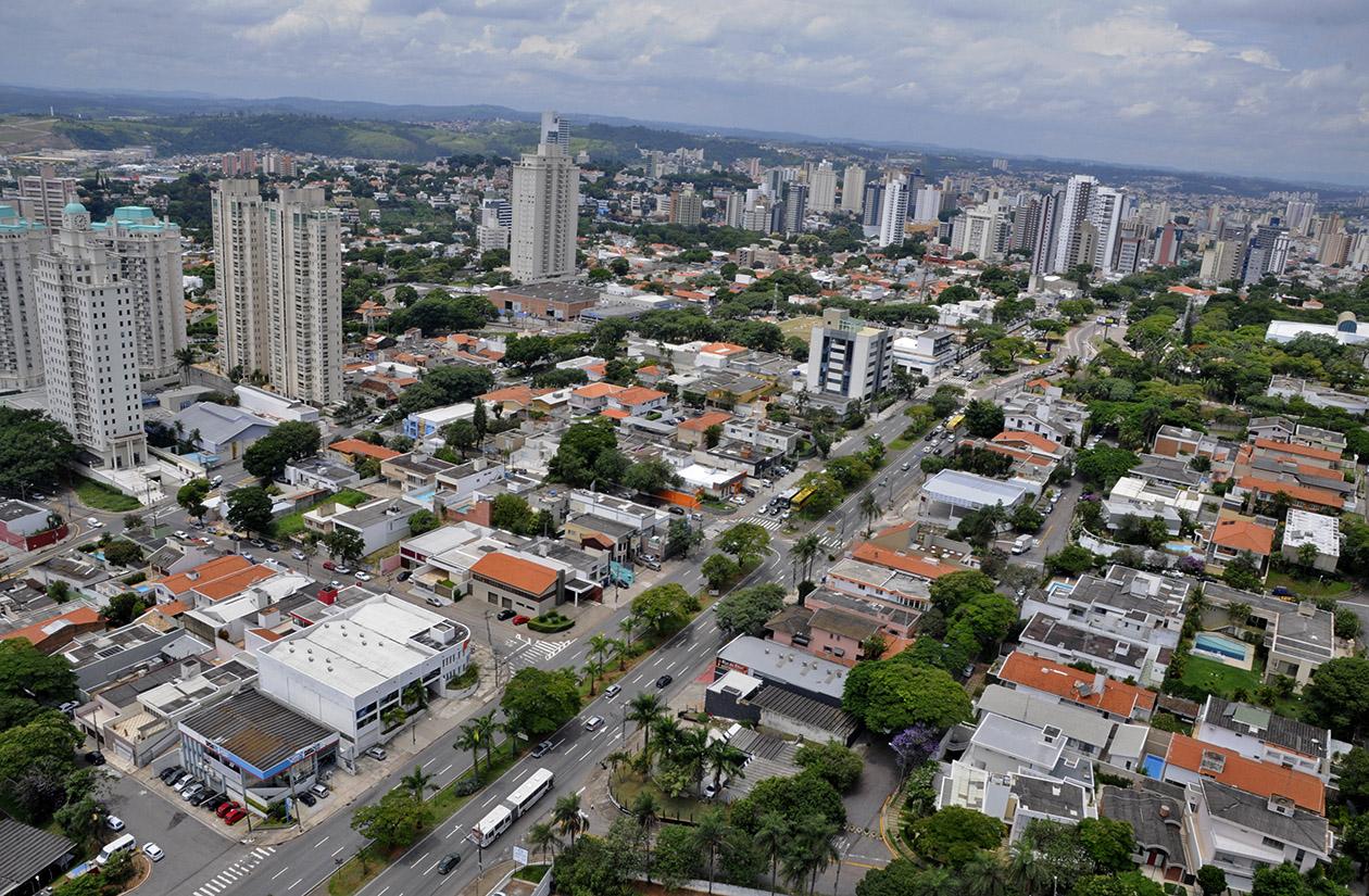 Foto aérea de área urbana, em que se veem telhados, prédios, ruas e arborização