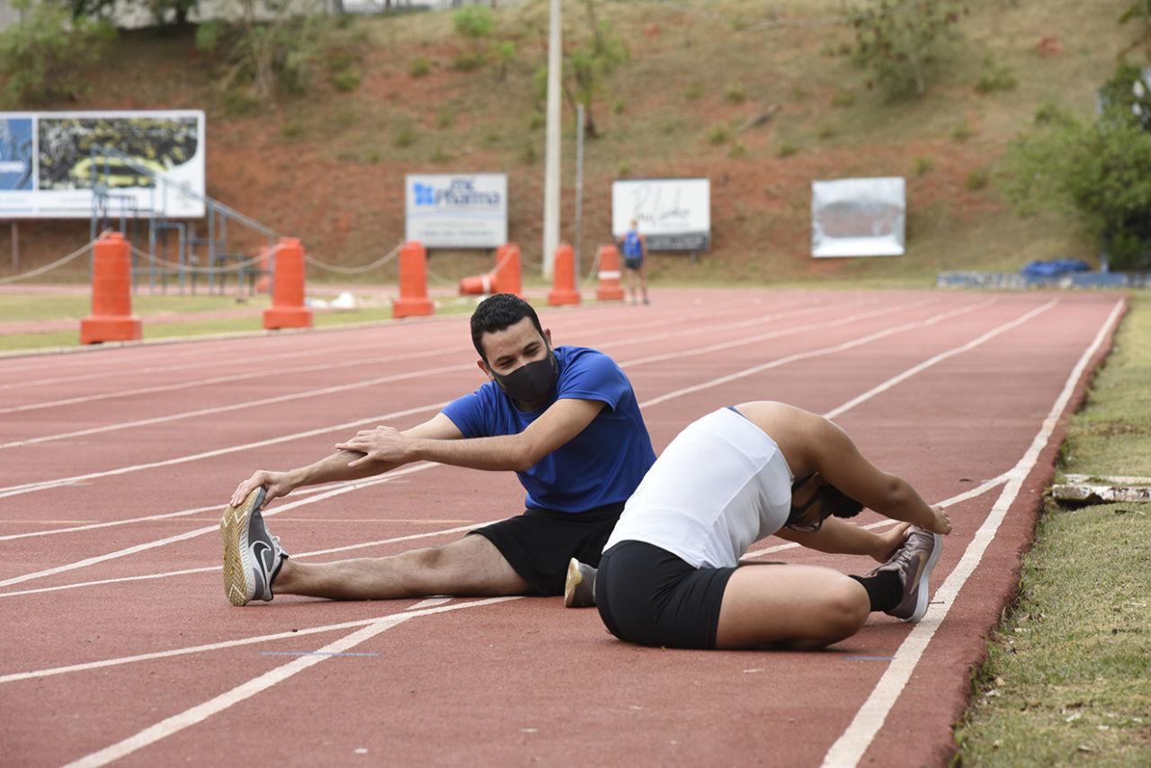 Homem e mulher usando máscaras, sentados sobre pista de caminhada, fazendo alongamento