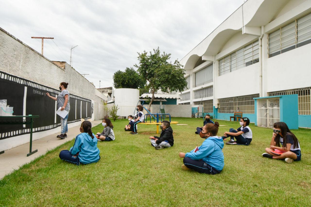 Crianças aprendem no gramado da escola Pedro de Oliveira