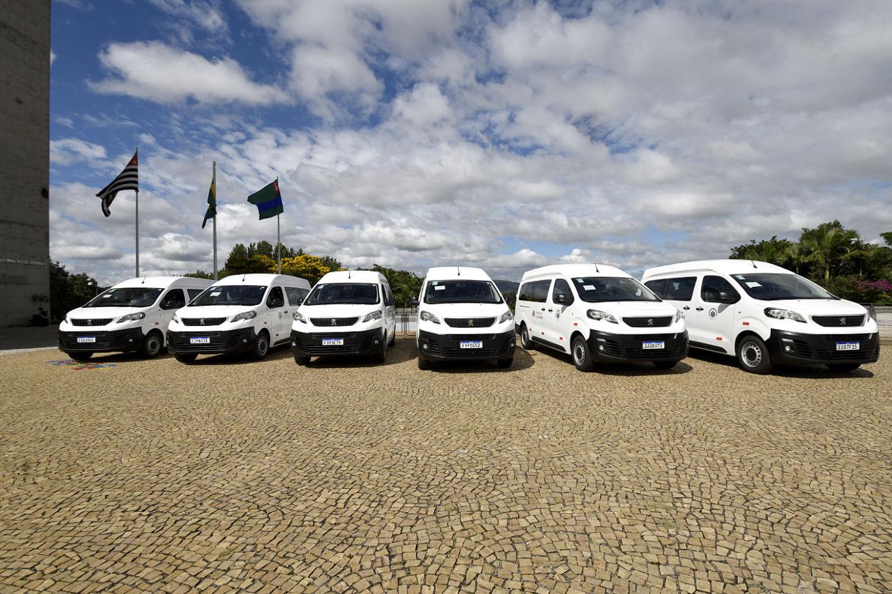 Imagem mostra seis veículos brancos Peugeot Expert Eurolaf , céu com nuvens e bandeiras ao fundo