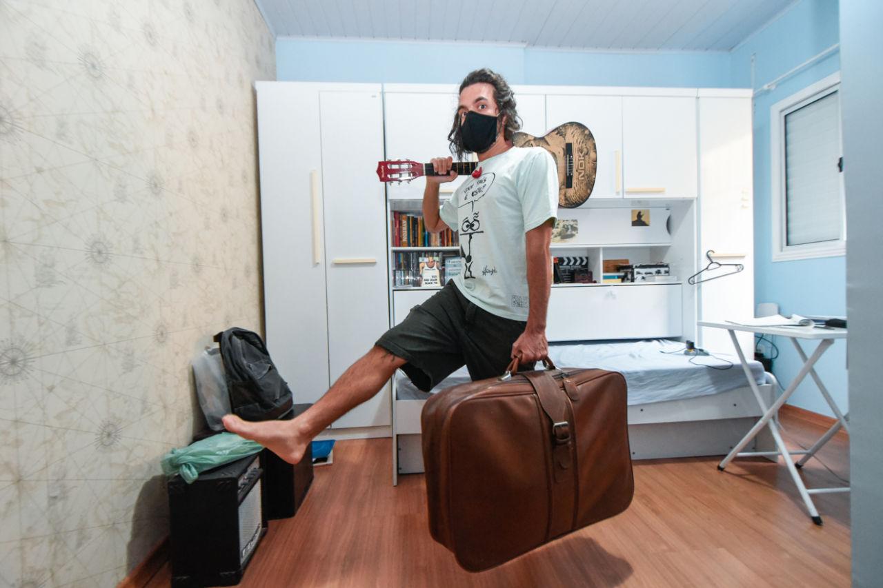 Rapaz com camiseta, bermuda e máscara segura uma mala com a mão esquerda, um violão sobre o ombro direito e se equilibra com a perna direita para o alto.