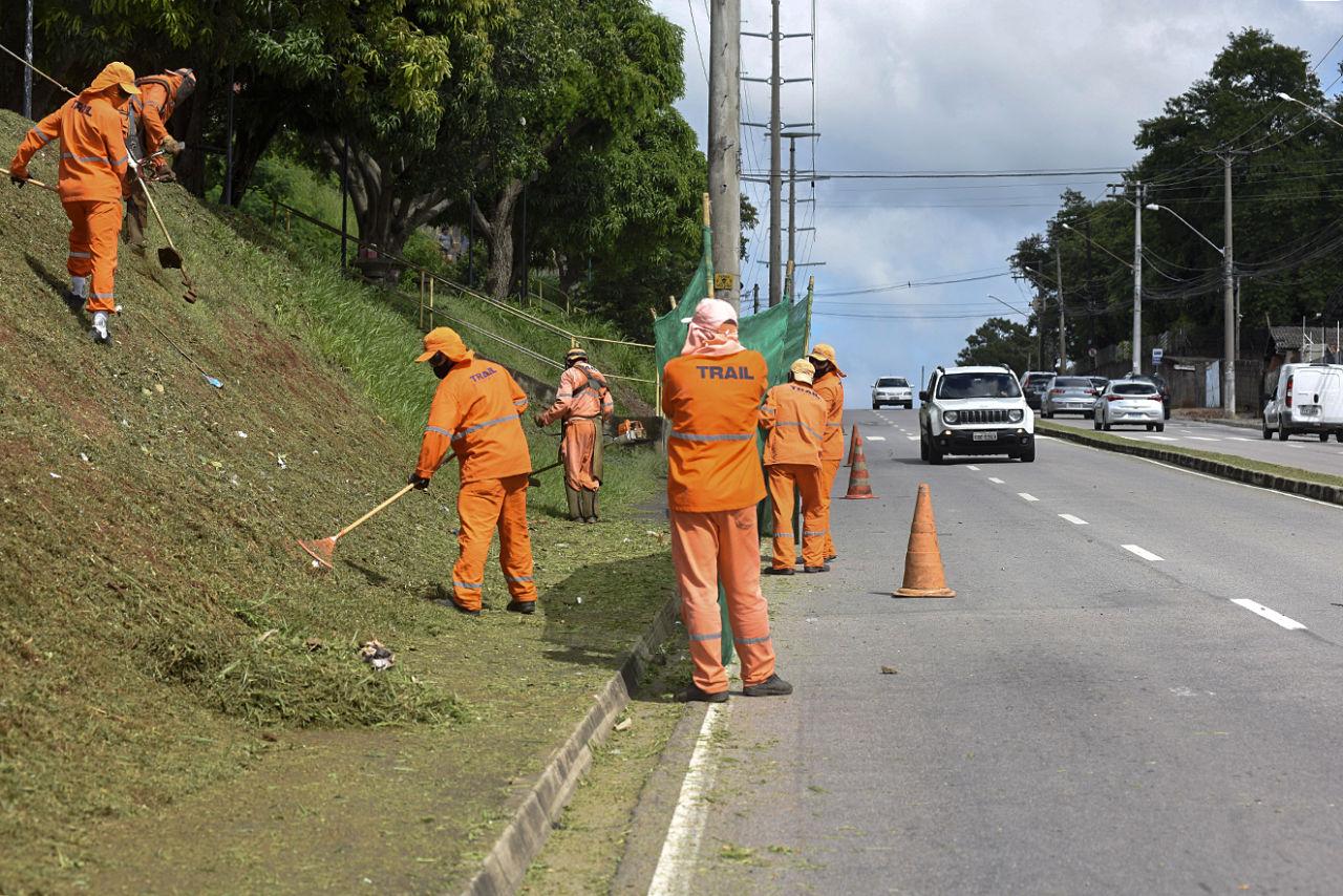 Imagem mostra avenida e morro na lateral. Homens com roupa laranja fazem o corte do mato e limpeza, enquanto outros seguram rede verde para segurança
