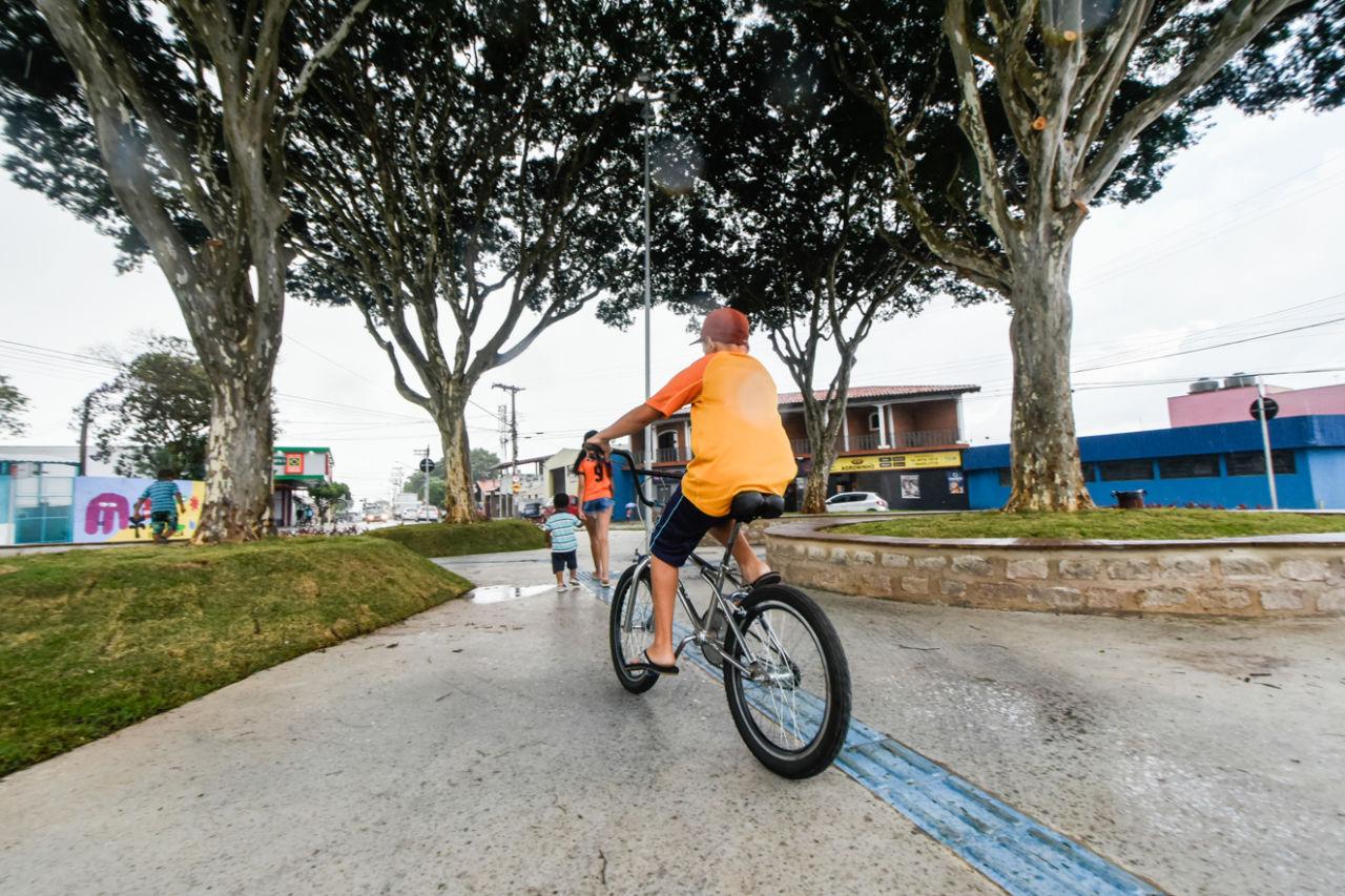Menino usando boné passa de bicicleta entre árvores de uma praça, onde há também outras crianças