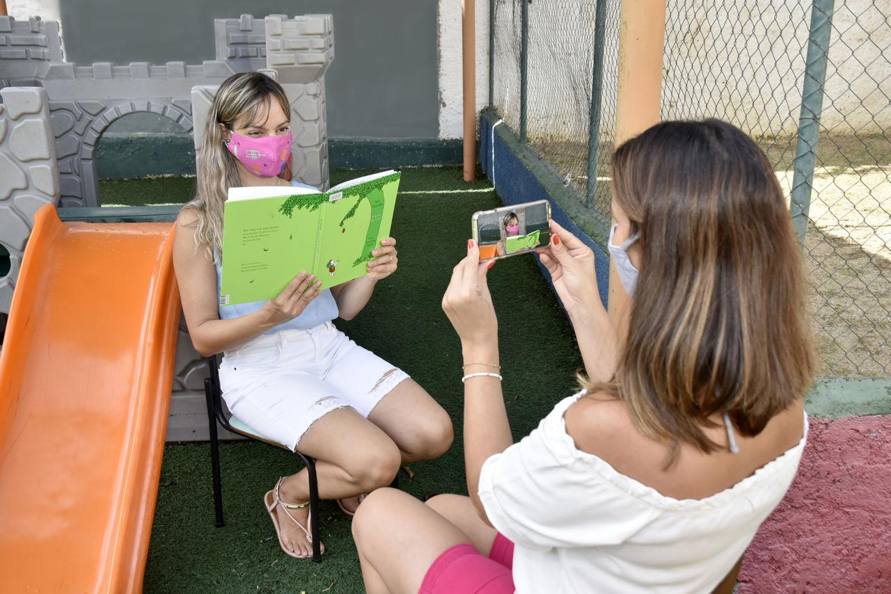 Imagem mostra duas mulheres sentadas em um parquinho infantil. Uma delas segura um livro enquanto a outra faz vídeo por celular.