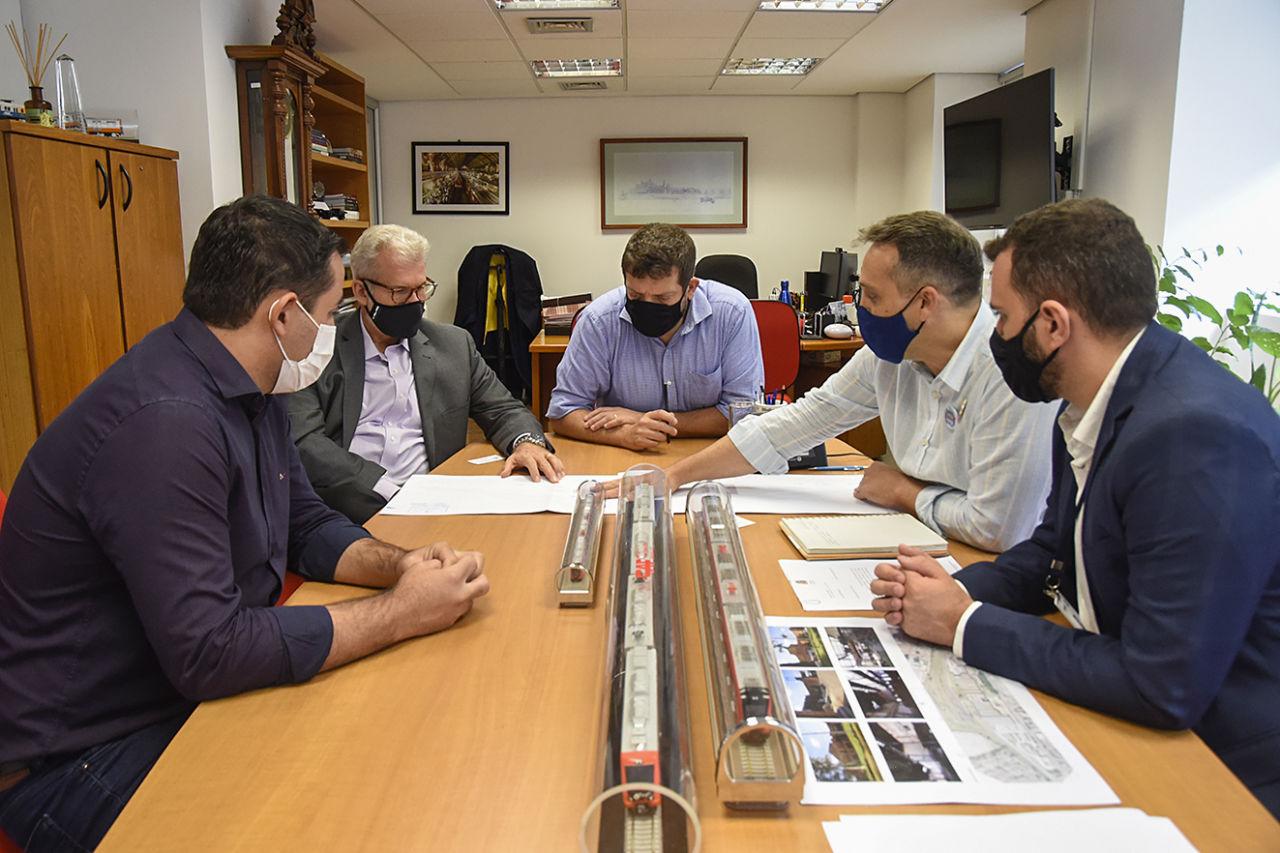 Cinco homens usando máscaras e sentados em torno de uma mesa retangular dialogam, apoiados e olhando para mapas e fotos sobre a mesa, onde há também três miniaturas de vagões de trens.