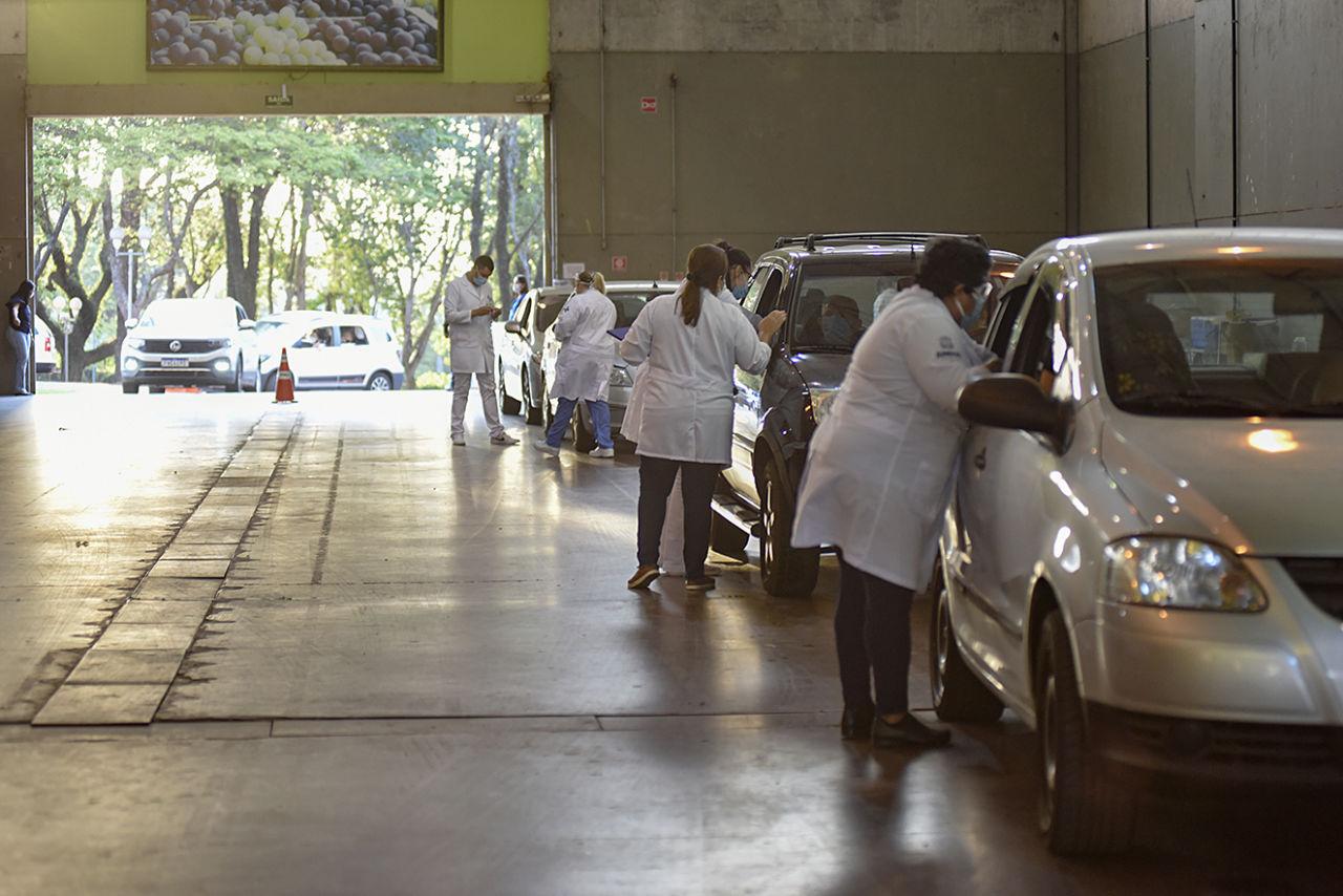 Fila de carros dentro de galpão, com profissionais da saúde com roupas brancas abordando as pessoas nas janelas