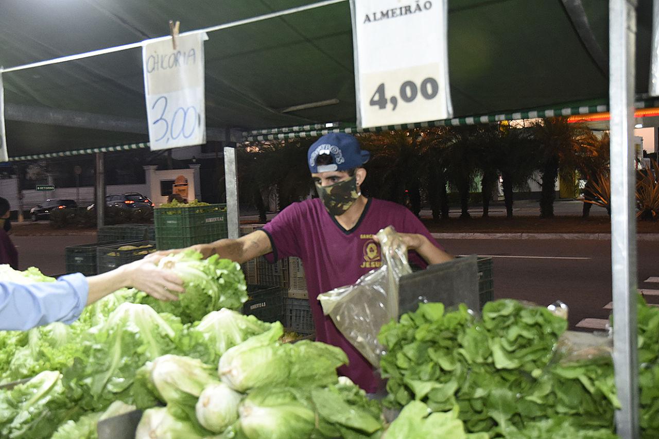 Homem usando máscara atrás de barraca de feira entrega verduras a uma mão