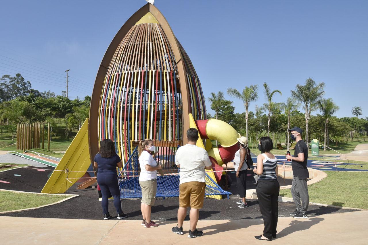Pessoas de costas, em formato de semi-círculo, conversam em frente a um brinquedo infantil de tamanho superior ao das pessoas, em formato de foguete