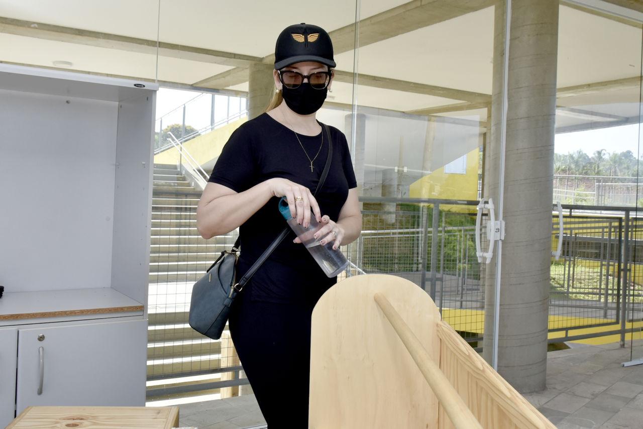 Mulher usando máscara e boné, segurando uma garrafa d'água, observa objetos de madeira