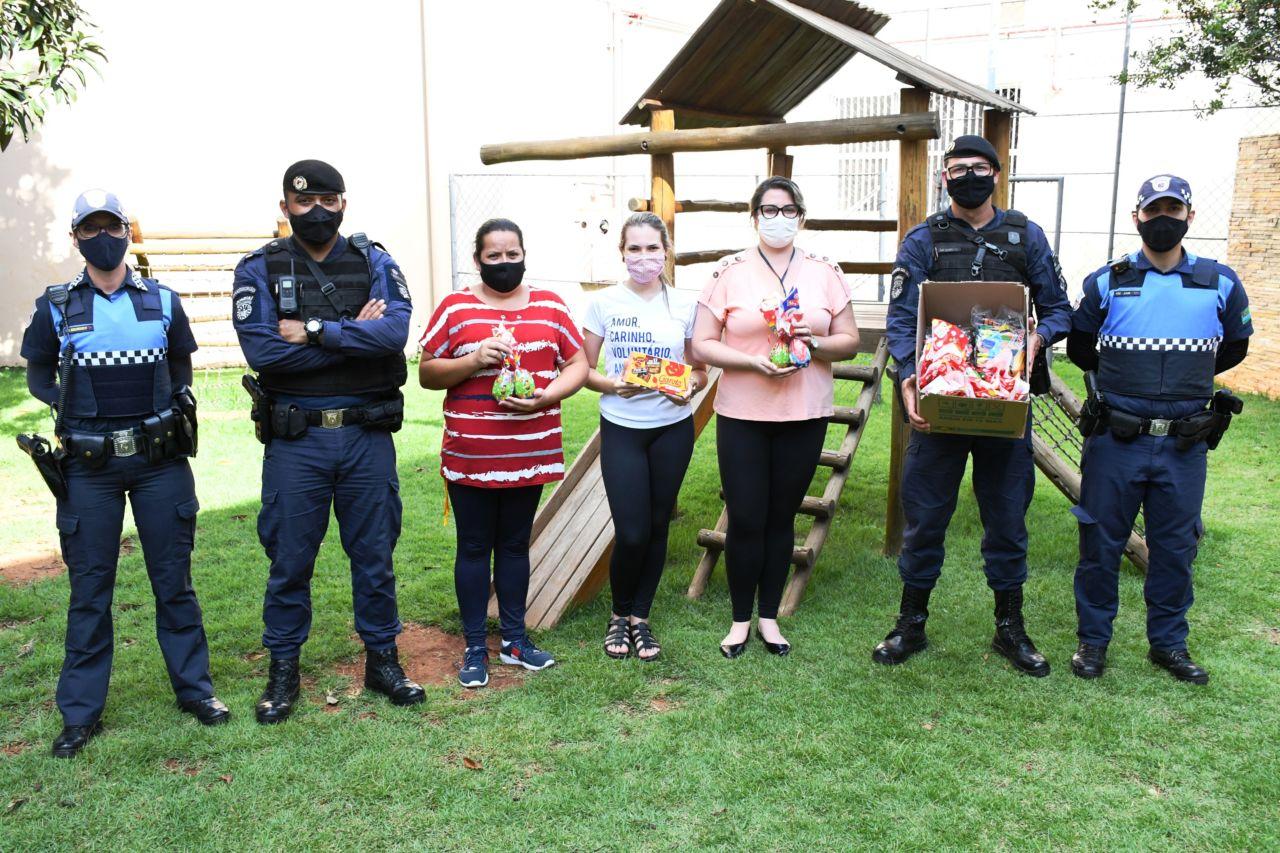 Homens e mulheres fardados e mulheres com roupas civis, todos usando máscaras, em foto posada, perfilados, com caixas de chocolates nas mãos