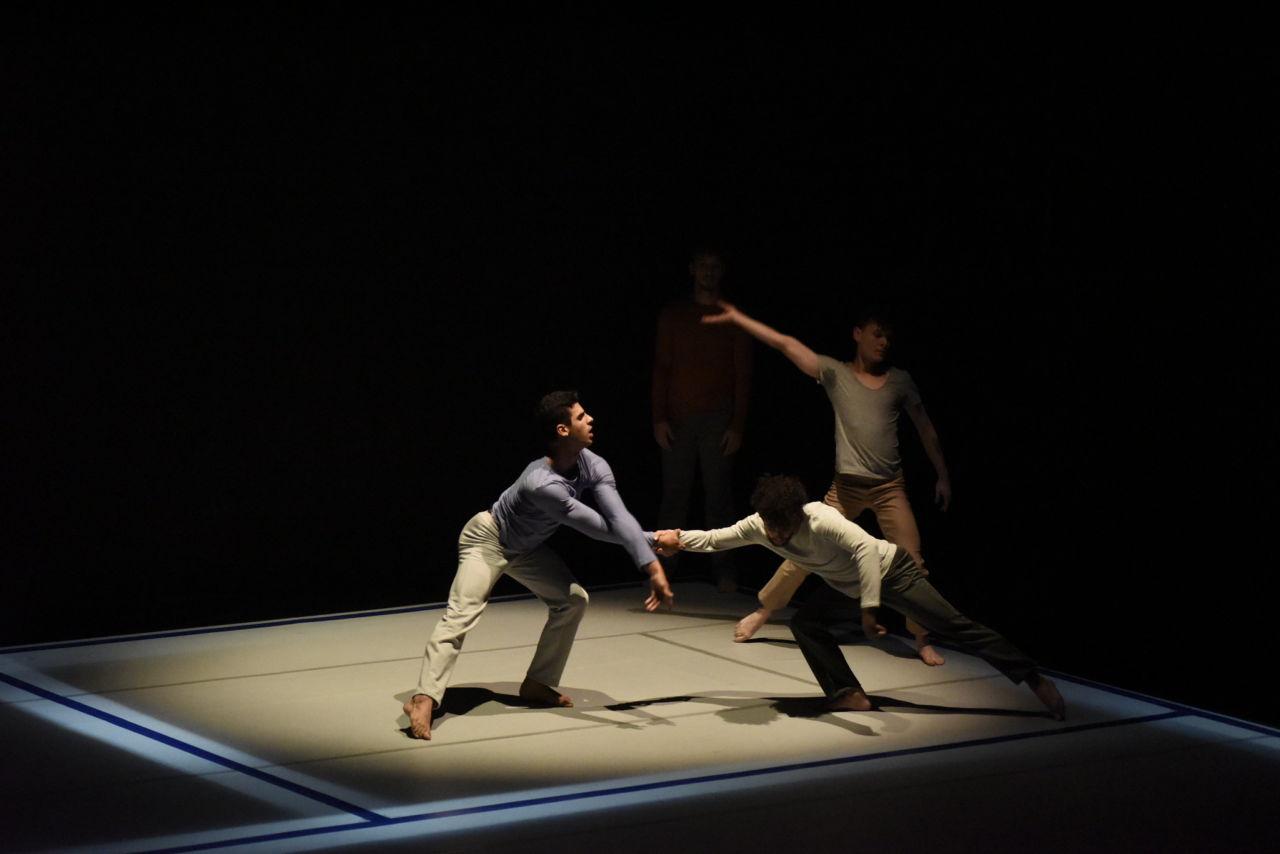 Quatro bailarinos fazem performance sobre palco iluminado em ambiente escuro