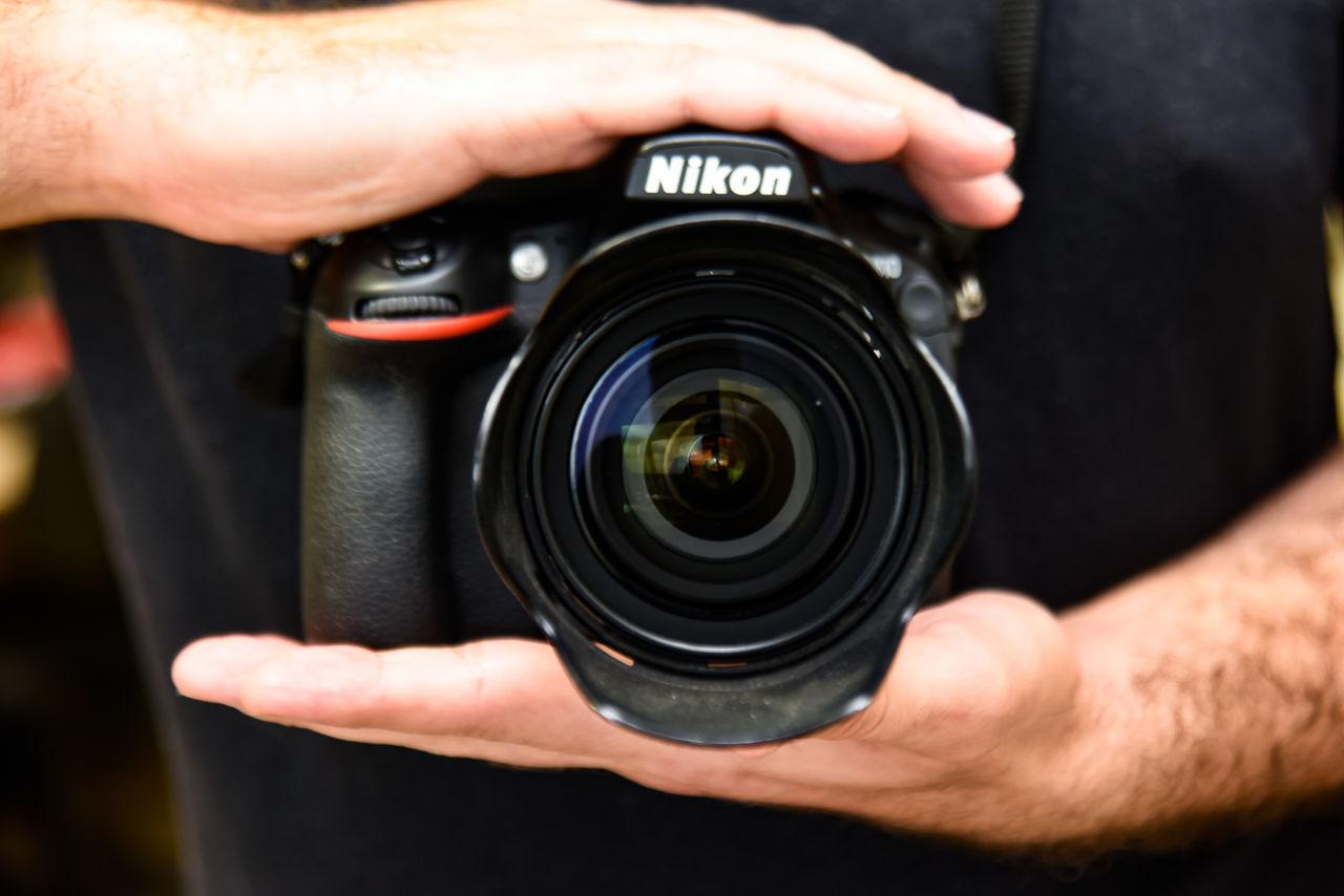 Mãos masculinas seguram, paralelas, uma câmera fotográfica