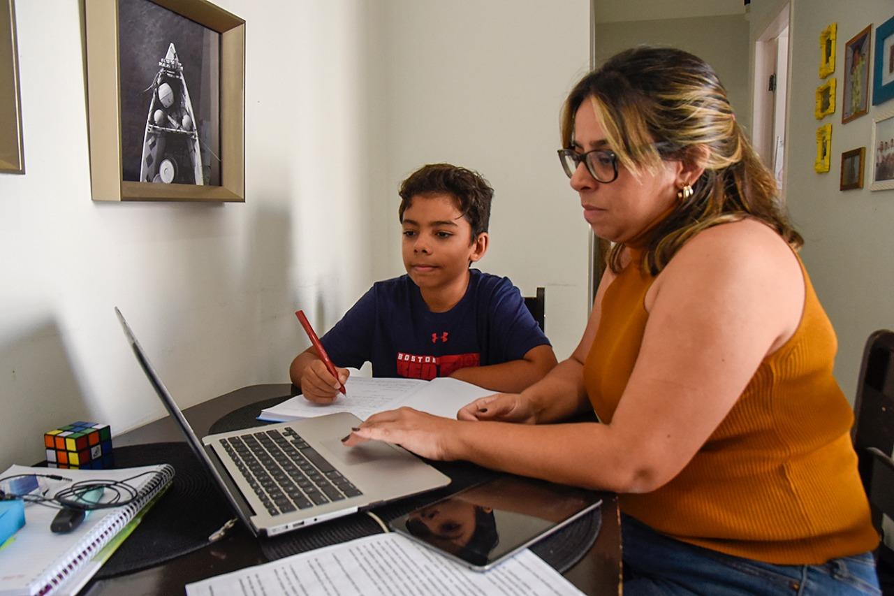 Imagem mostra criança e mulher (filho e mãe) em frente a um computador. Eles estão assistindo à aula em sistema remoto.