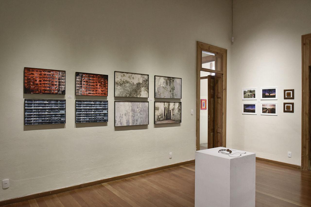 Sala de exposições, com quadros, fotos, porta e bloco retangular branco ao centro com colar exposto