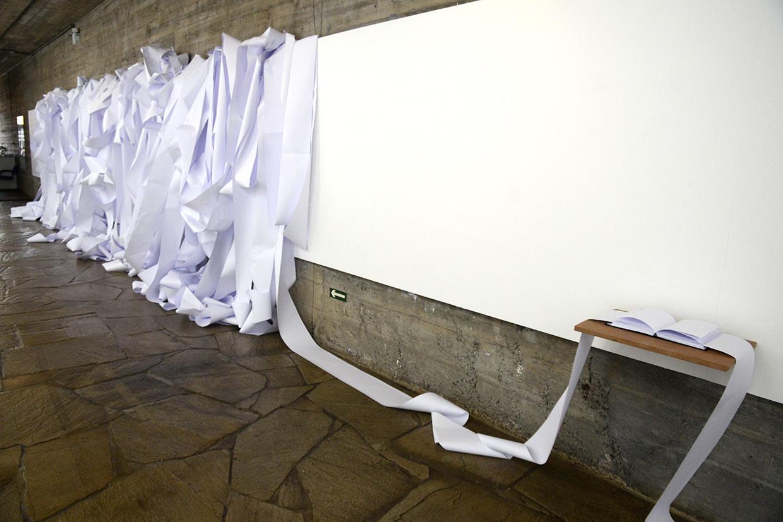 Parede branca de galeria de exposição com diversos rolos de papel branco estendidos e pendurados sobre painel, que caem e viram um rolo só integrado a um livro aberto sobre uma pequena prateleira