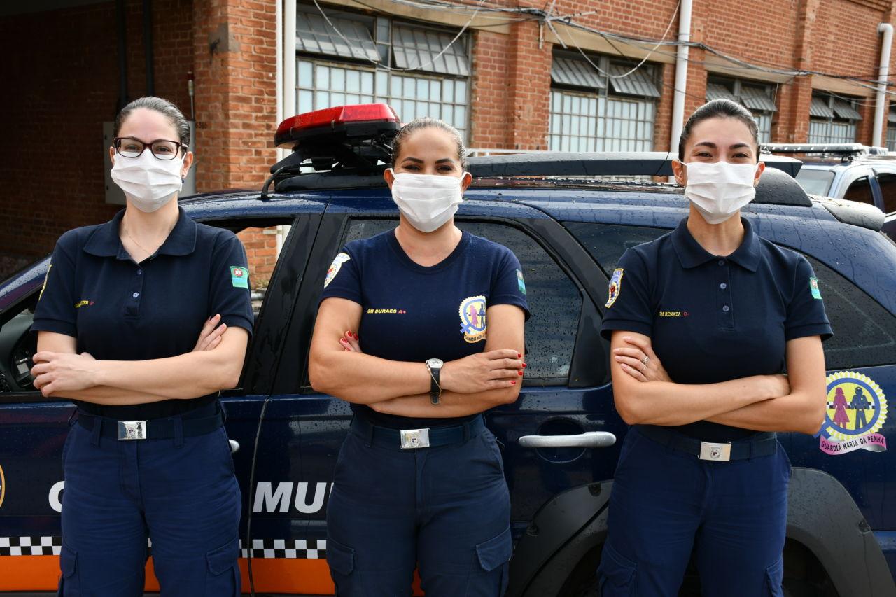 Três mulheres fardadas e usando máscaras, posicionadas com os braços cruzados  em frente a uma viatura policial, com prédio de janelas e tijolos à vista ao fundo