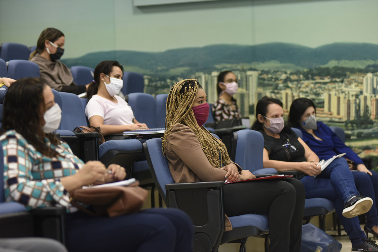 Mulheres usando máscaras, sentadas de modo espaçado em poltronas de auditório