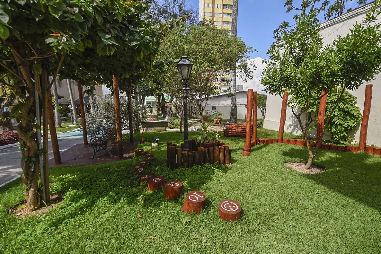 Jardim de residência antiga, com gramado, árvores, banco sob pergolados com plantas e peças de madeira envernizada