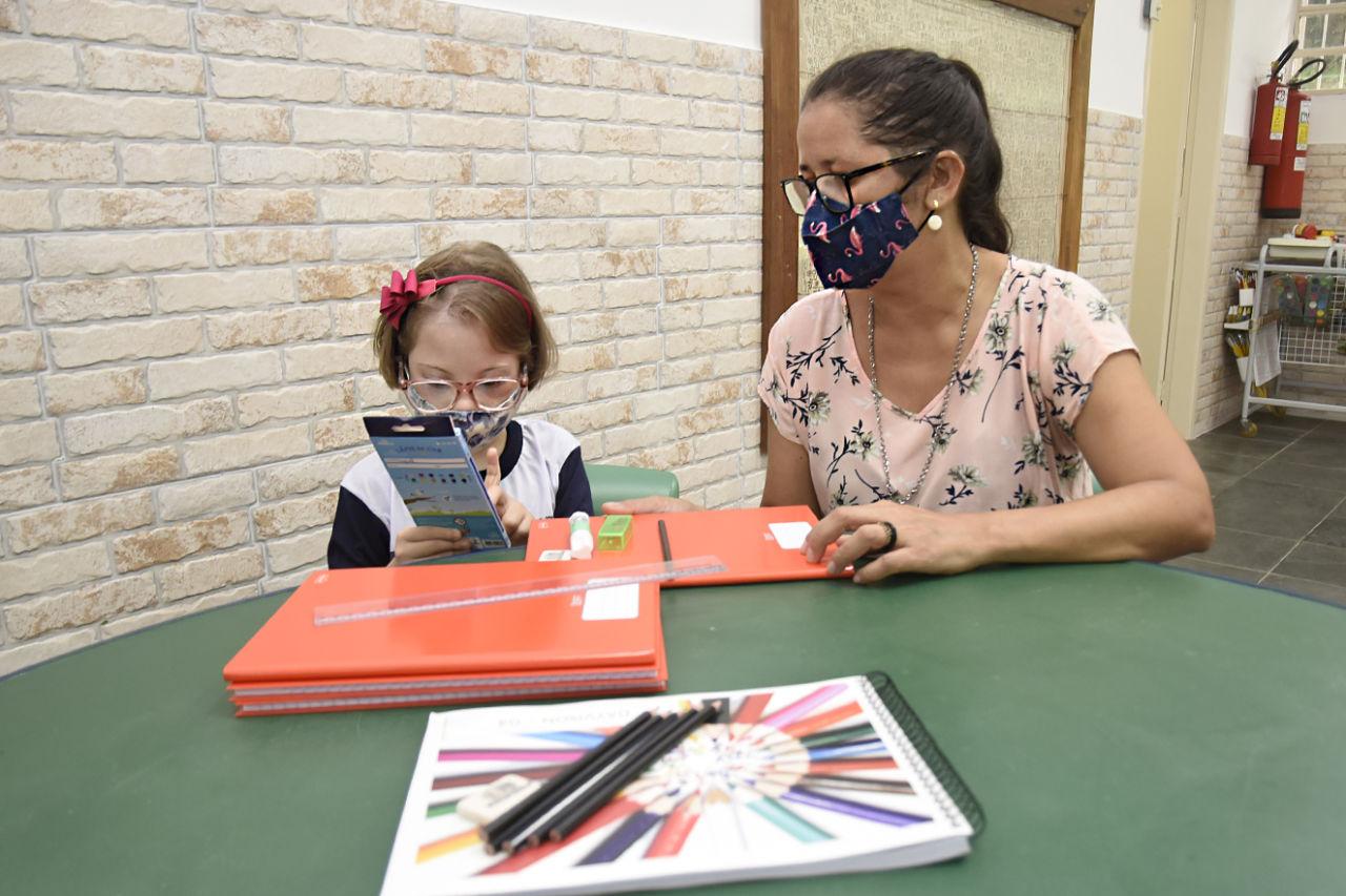 Criança olhando caixa de lápis e mulher ao lado