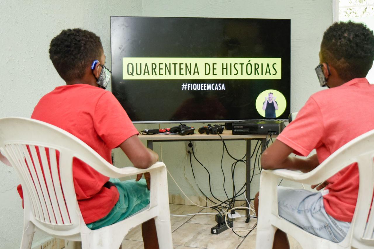 """Duas crianças de costas, sentadas em cadeiras, assistindo a uma tela de televisão em que se lê """"Quarentena de histórias - #Fiqueemcasa"""" e se vê um homem no canto da tela"""