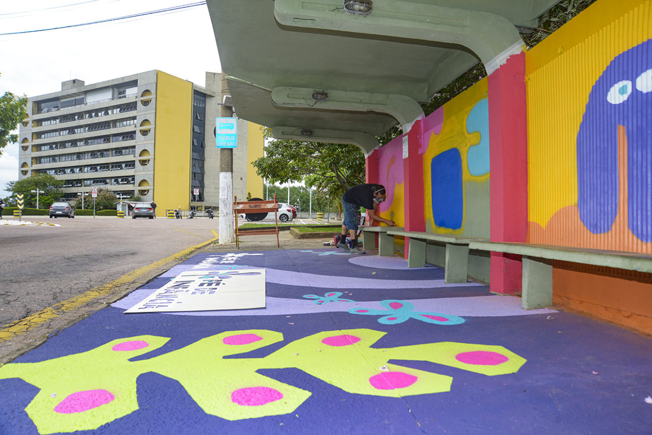 Homem faz pintura colorida sobre chão e ponto de ônibus de alvenaria, com prédio ao fundo