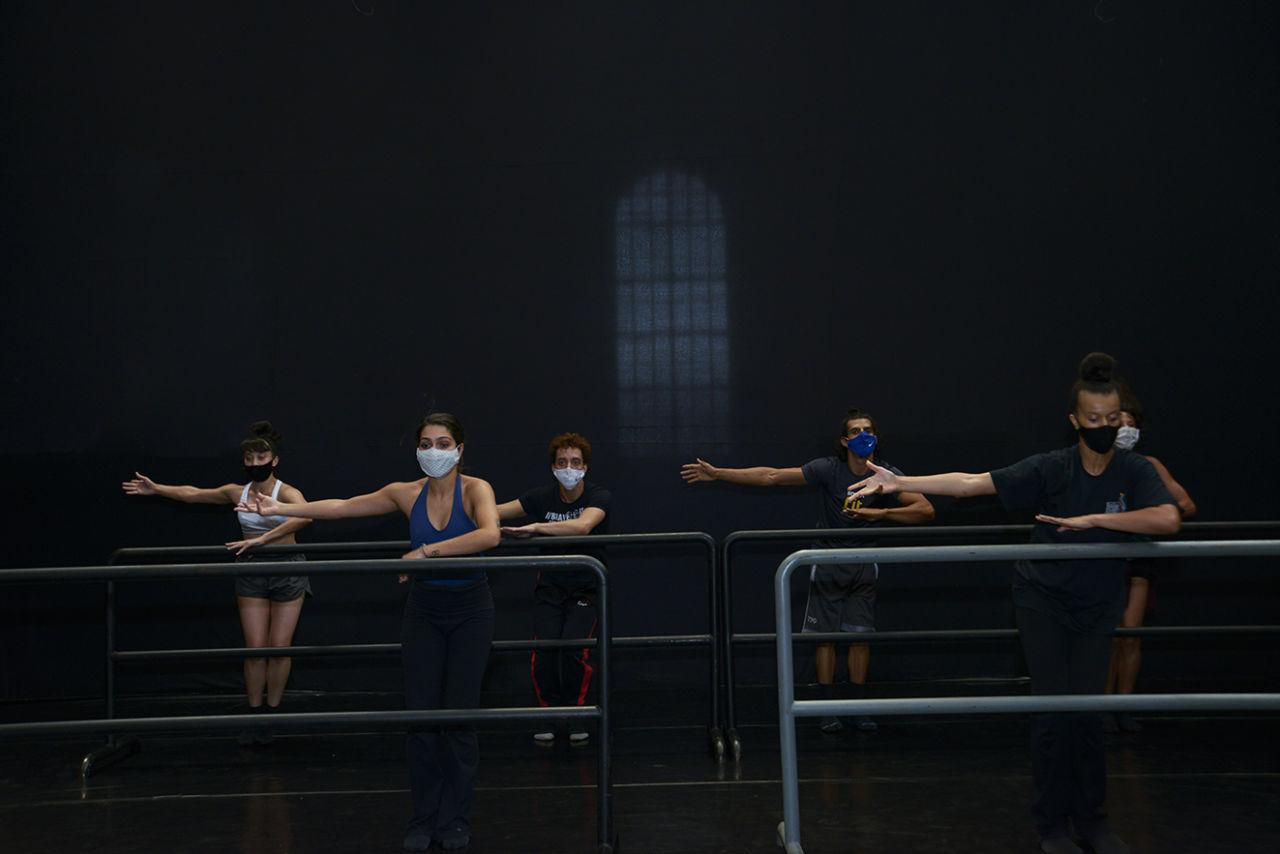 Seis bailarinos usando máscaras fazem exercício apoiando uma mão sobre barra e a outra levantada, em palco com tela escura ao fundo