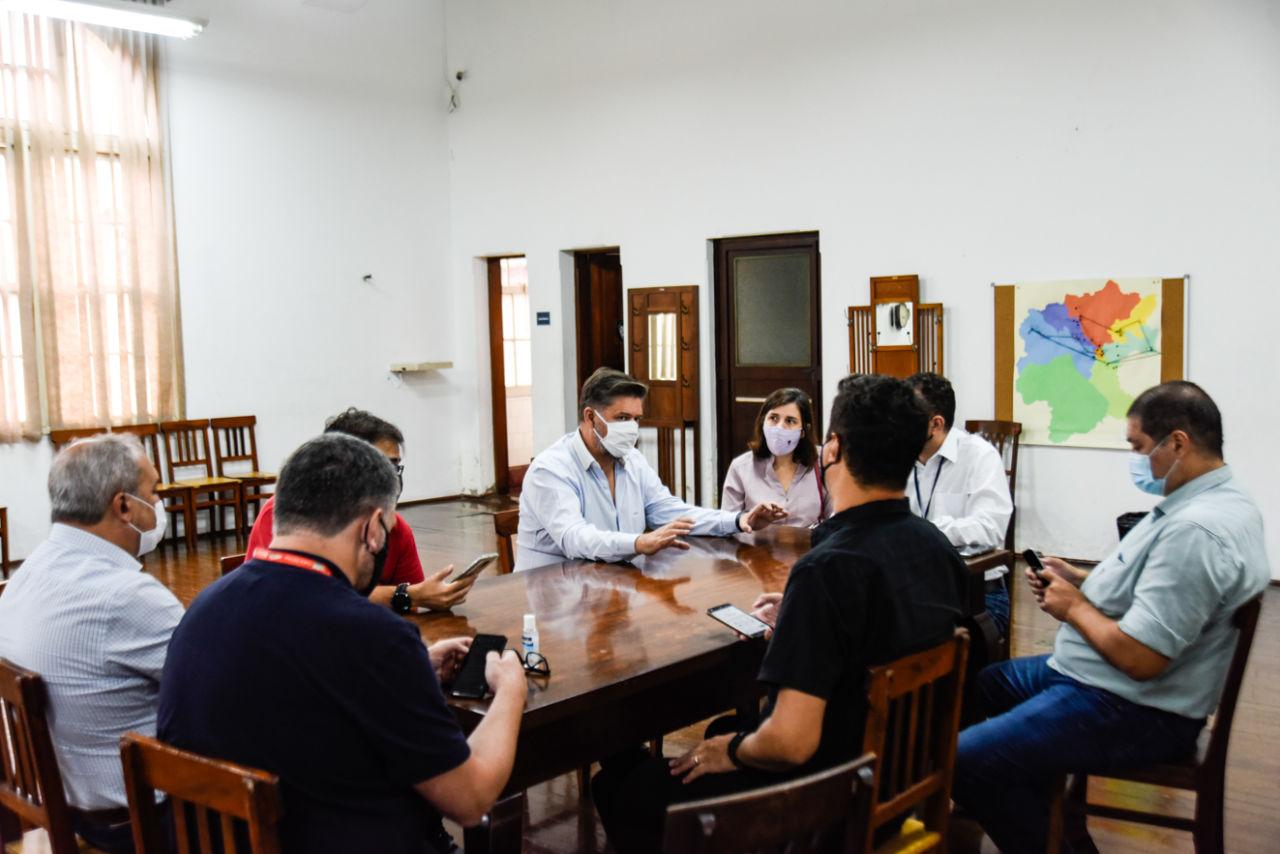 Pessoas usando máscaras, sentadas no entorno de uma mesa de madeira