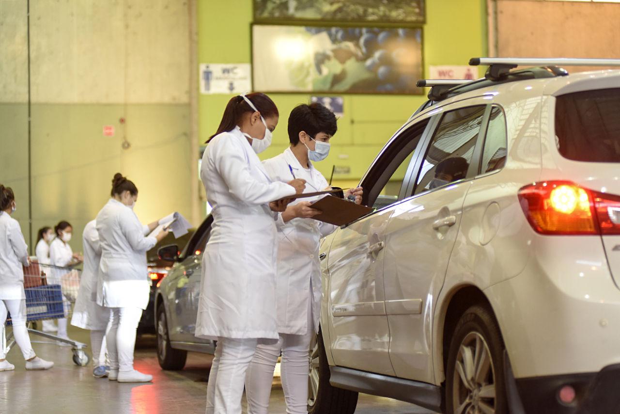Mulheres usando jalecos de profissionais da saúde e máscaras abordam veículos, dentro de galpão