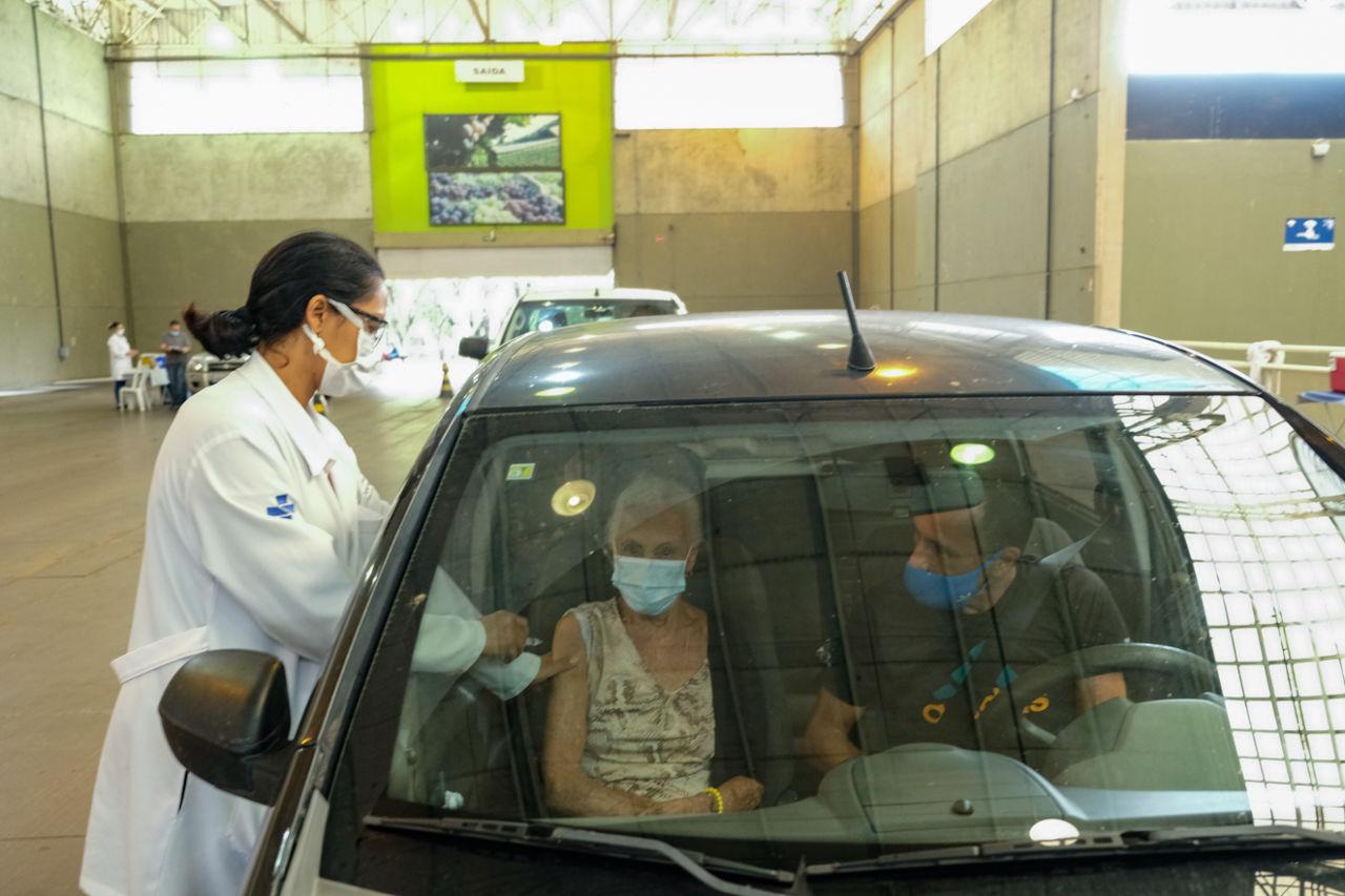 Mulher com jaleco de profissional da saúde aplica vacina em mulher de cabelos brancos sentada no banco de passageiro de carro com homem motorista ao lado. Todos usam máscaras e estão dentro de grande galpão coberto