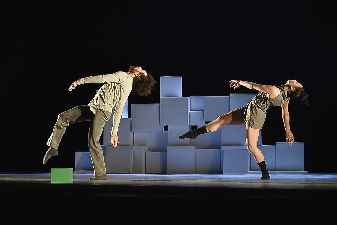 Um bailarino e uma bailarina dançando sobre palco, apoiados sobre um dos pés. com o tronco inclinado e um braço na horizontal e outro apontado para baixo, com cubos iluminados no fundo