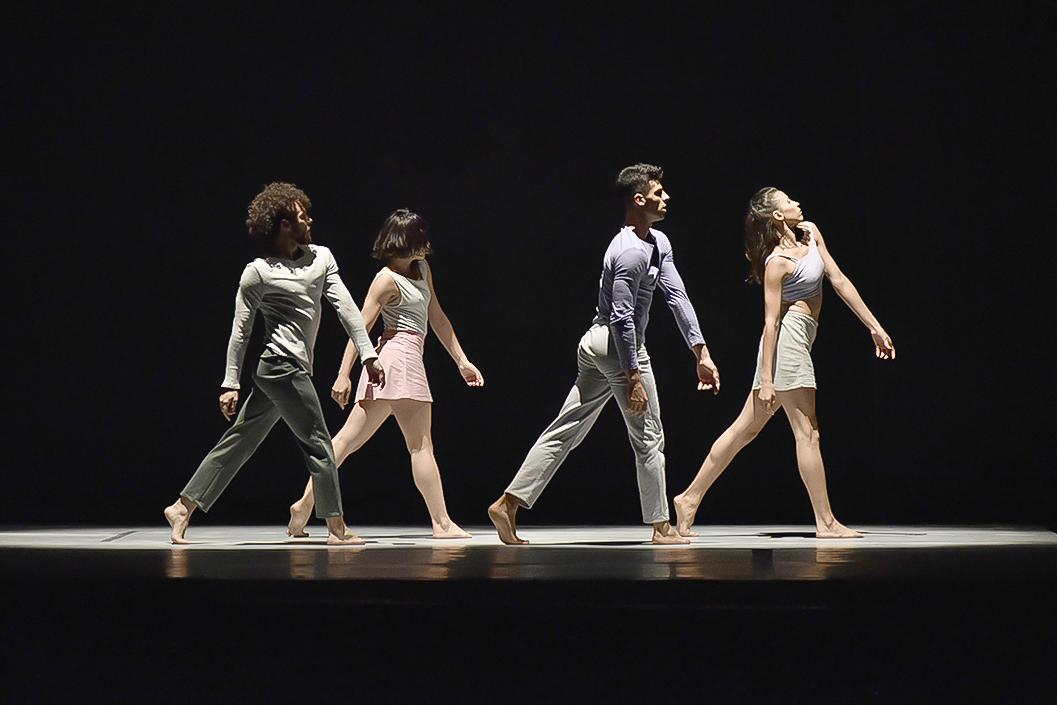 Dois bailarinos e duas bailarinas dançando sobre palco escuro, sob foco de luz