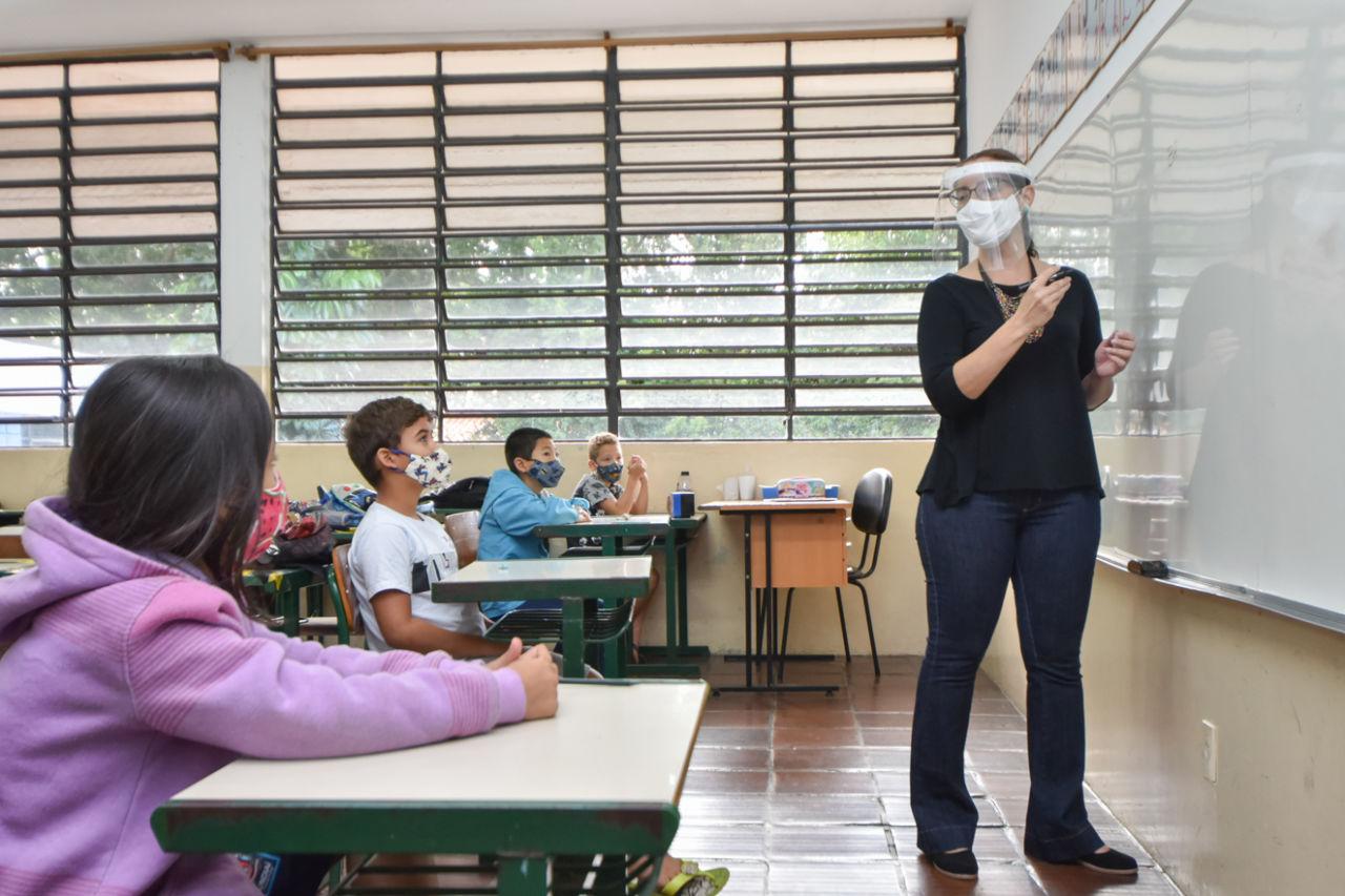 imagem mostra sala de aula com professora à frente,  usando máscara e face shield; quatro alunos estão com distanciamento social e usando máscaras.