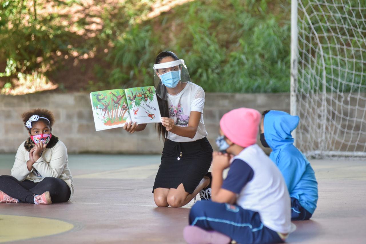 Três crianças usando máscaras sentadas em formato de círculo sobre quadra esportiva, olhando para livro segurado por uma mulher adulta usando saia, máscara, face shield transparente sobre o rosto e cabelo preso e apoiado sobre o ombro direito.