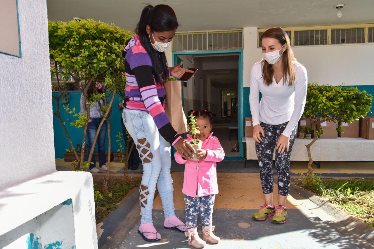 Imagem mostra menina de um ano, com muda de planta na mão, no meio de duas mulheres. Ao lado direito a mãe com sacola de papelão na mão e ao lado esquerdo professora.  Ambas as adultas usam máscara facial.
