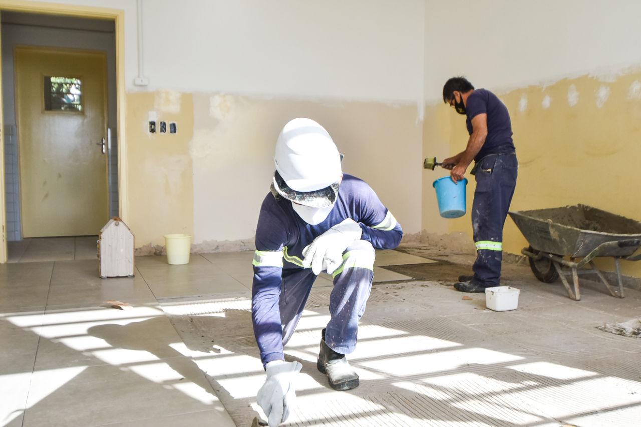Imagem mostra sala em reforma, homens fazem assentamento de piso.