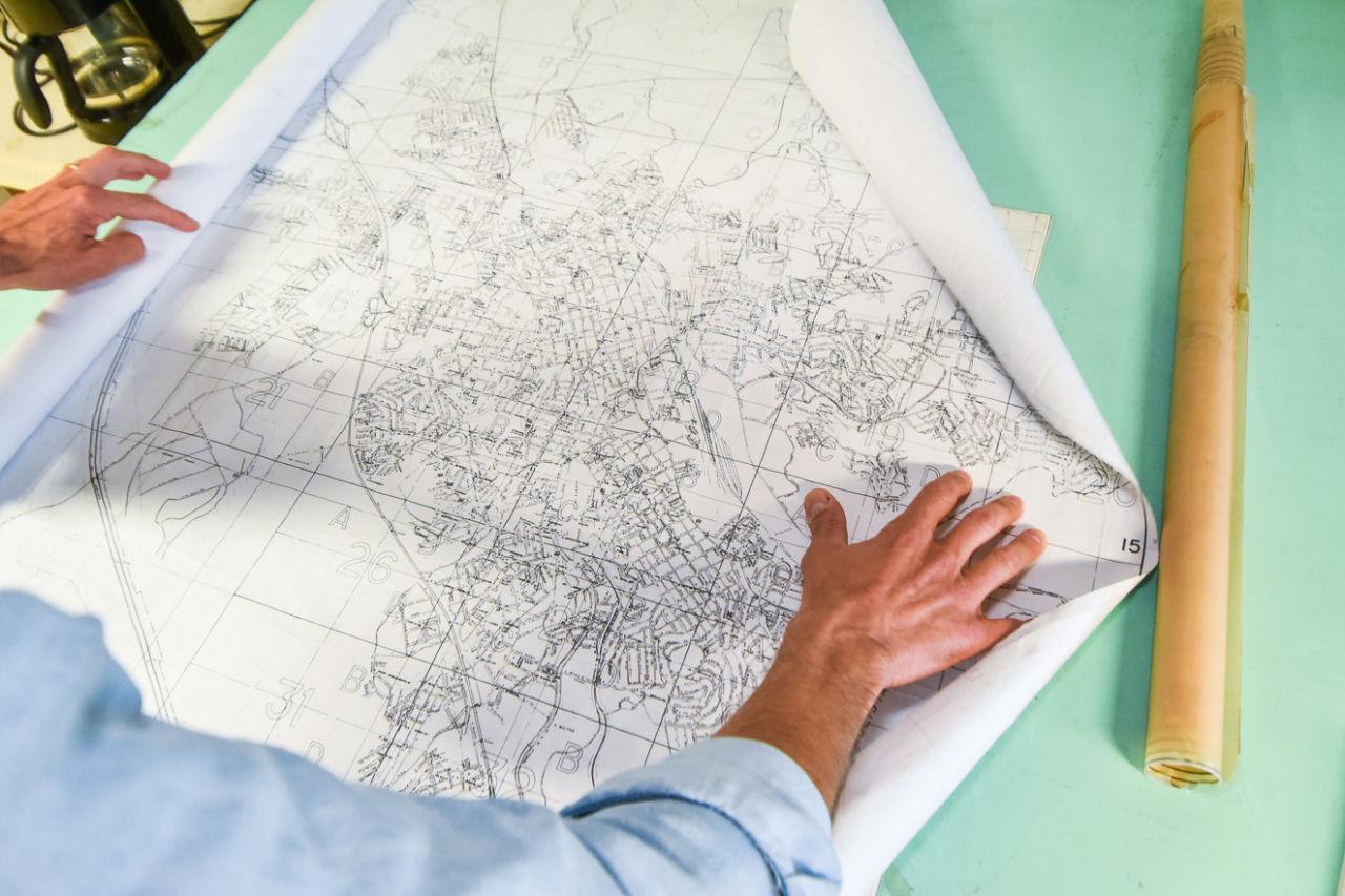Homem abre um mapa sobre uma mesa