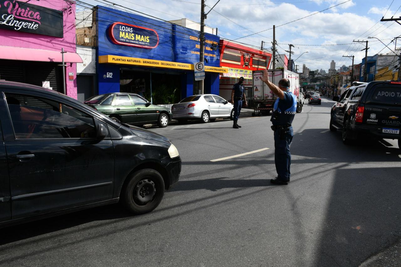 Dois homens fardados e usando máscaras conduzem fluxo de carros no meio de uma rua de comércios