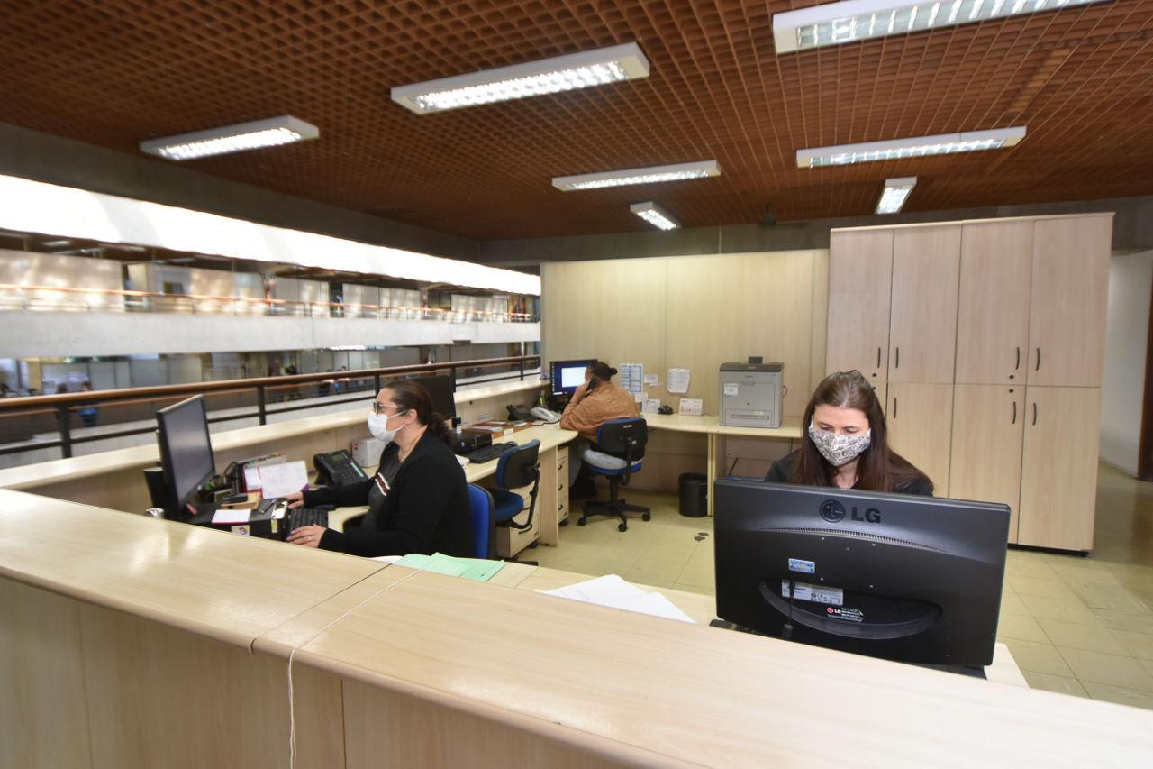 Três mulheres usando máscaras, trabalhando em escritório, em frente a mesa com computadores, telefones e papeis, com vão livre de prédio e outros setores ao fundo