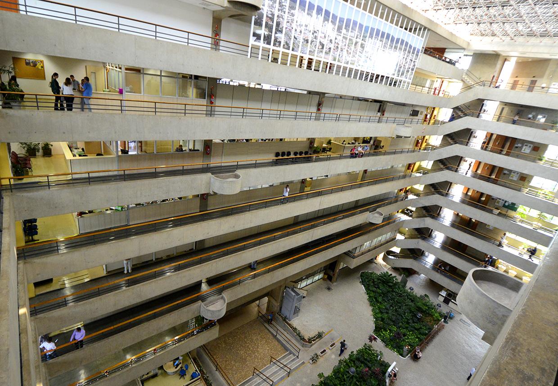 Vão livre de prédio, com oito andares com parapeitos e praça ao centro com jardim de folhagens
