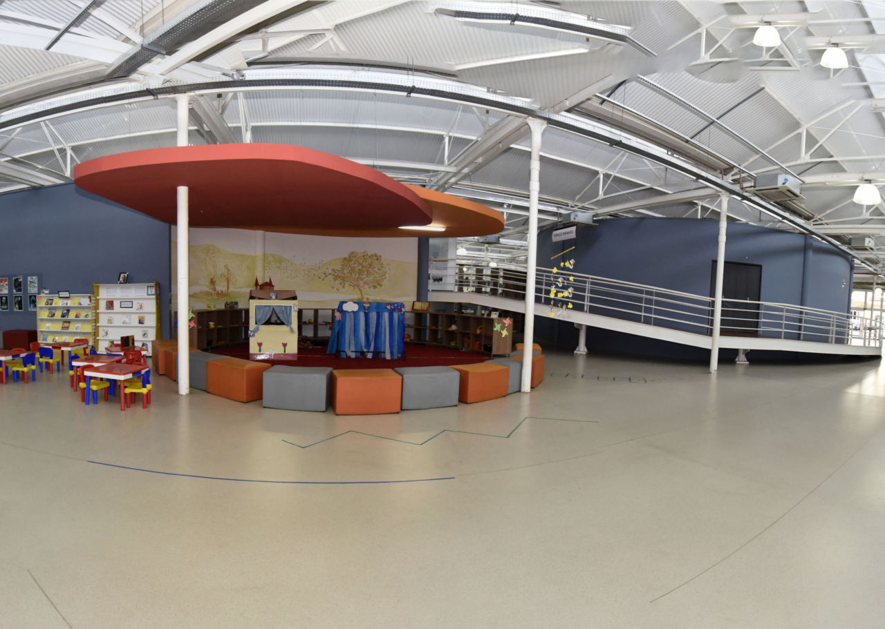 Imagem mostra espaço interna de biblioteca vazios. No canto esquerdo mesas e cadeiras coloridas para crianças, no centro pufs laranja e cinza em formato de roda no centro. No canto direito, construção com parede azul e corrimão branco (auditório interno)