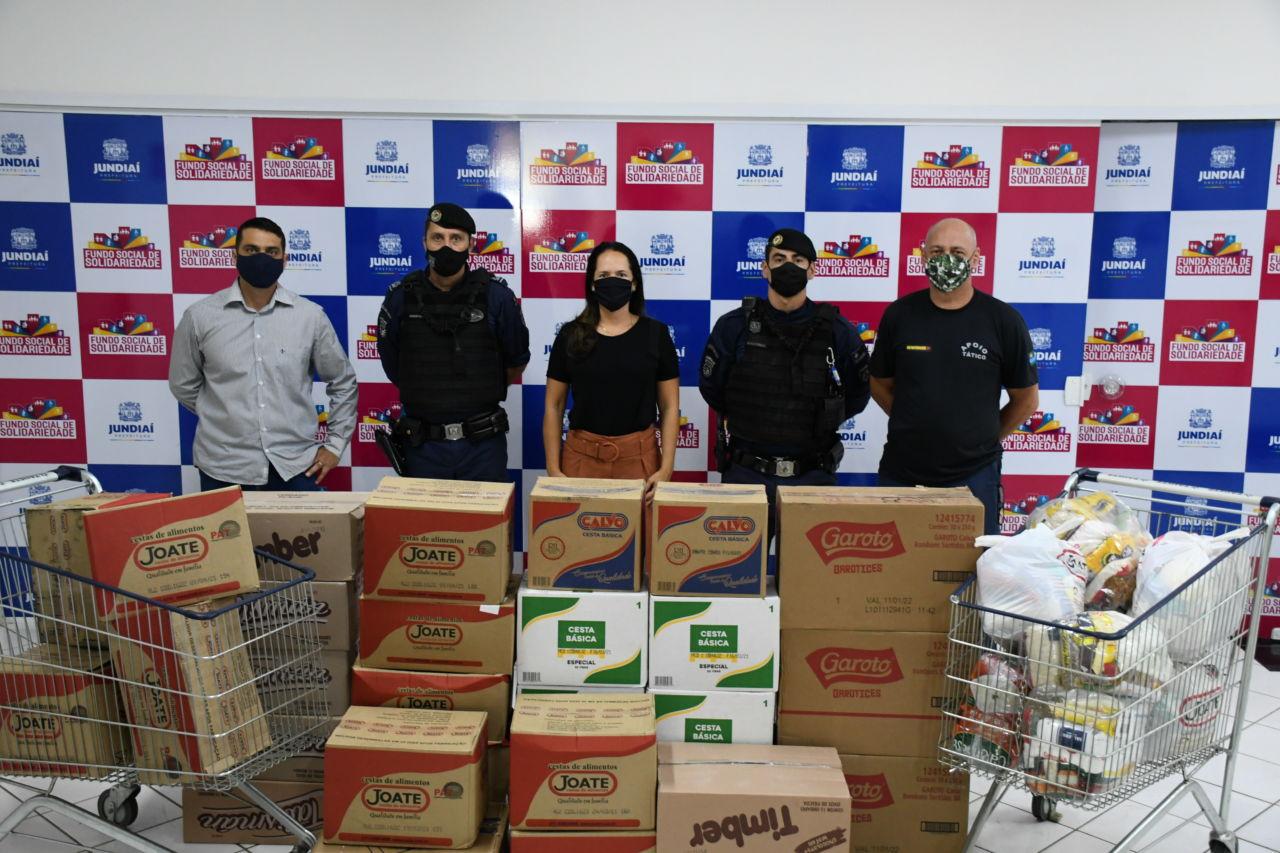 Uma mulher, dois homens com roupas civis e dois homens fardados, todos com máscaras, posicionados atrás de caixas de papelão e carrinho de metal de supermercado, com sacolas de alimentos