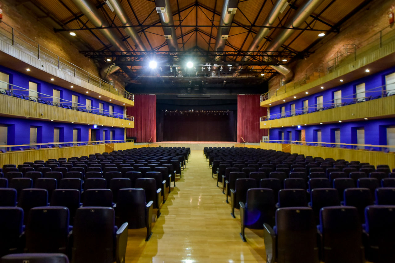 Sala de espetáculos de teatro vazio, vista da altura da plateia, em direção ao palco com cortinas abertas