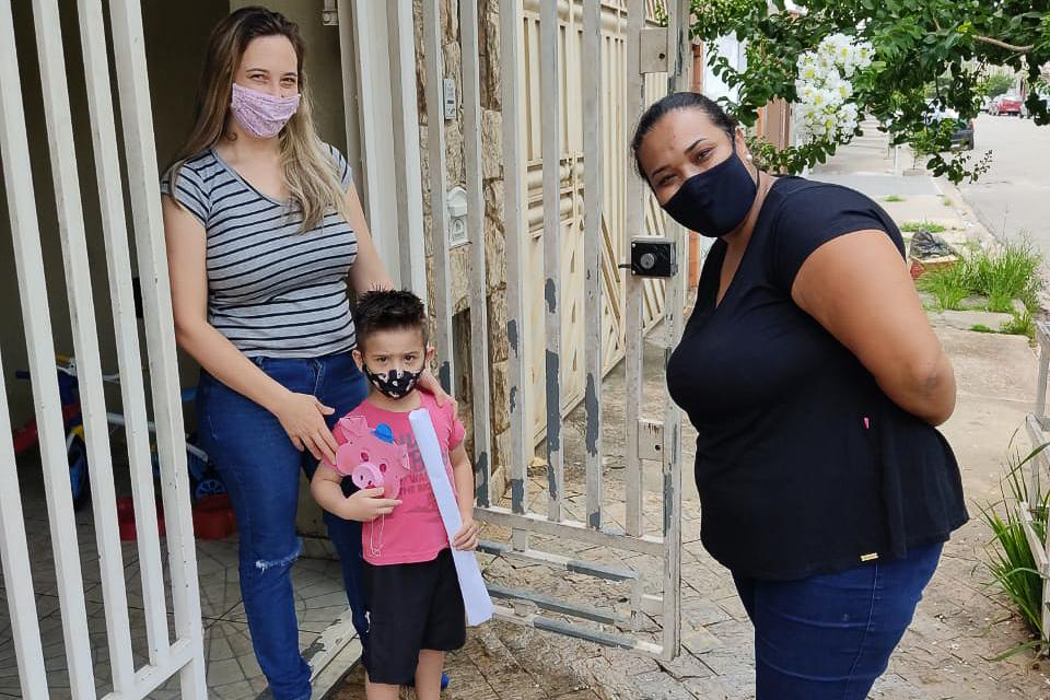 Imagem mostra duas mulheres e uma criança, que segura um papel e uma máscara de porquinho. Eles estão com máscara e em frente a um portão aberto.
