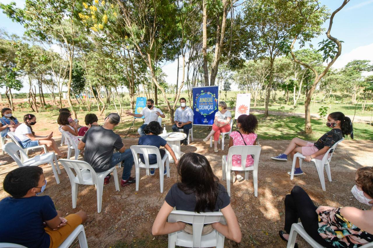 Crianças de diversos tamanhos sentadas em cadeiras de plástico em frente a três adultos, todos usando máscaras, sob a sombra de árvores