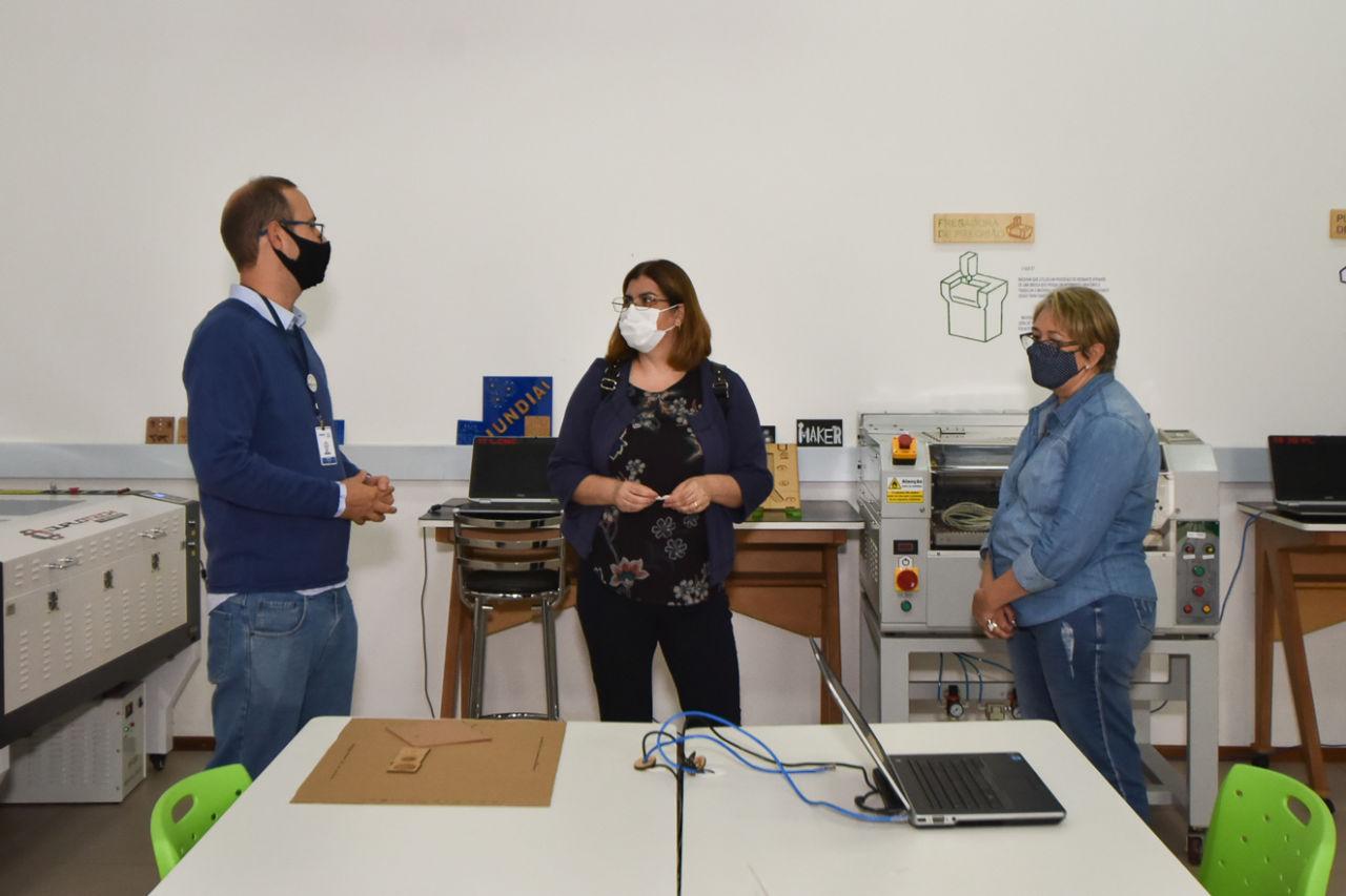 Imagem mostra homem explanando para duas mulheres. Ao fundo, equipamentos e computador.